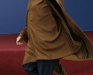 U.S. President George W. Bush wears a typical Peruvian poncho while walking to the group photo at the APEC summit in Lima