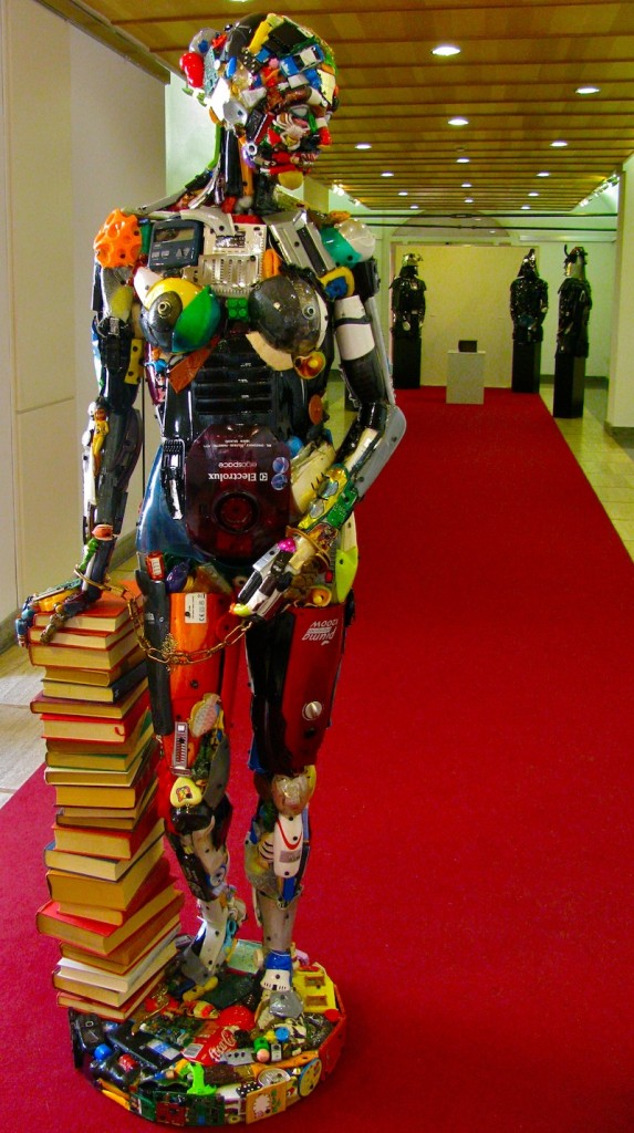 """Game of Cultures"" by artists DARIO TIRONI and KOJI YOSHIDA. Nude woman with a lust for books, in the background Samurai robots gather around a thick black book as if it were a shrine."
