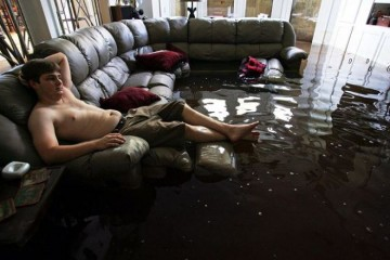 Eric Leese sits on a couch in his flooded living room in Metairie, outside New Orleans September 5, 2005. Thousands of residents of suburban New Orleans returned on Monday to inspect homes wrecked by Hurricane Katrina and President George W. Bush went back to the disaster zone to quell a political crisis over bungled aid efforts. Pictures of the Year 2005 REUTERS/Lee Celano FR05090007  ljc/VP - RTRMPX1