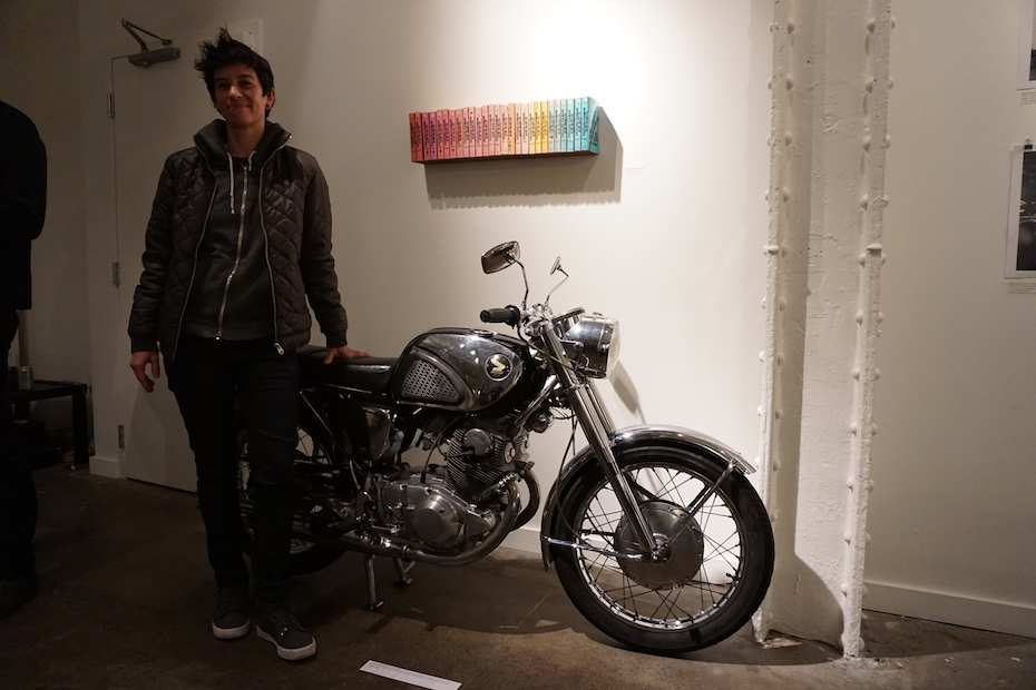 """Jennifer Tacy with her Honda Superhawk and 27 copies of """"Zen and the Art of Motorcycle Maintenance."""""""
