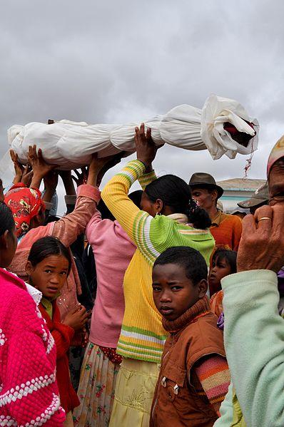 "Credit to <a href=""https://commons.wikimedia.org/wiki/File:Famadihana_reburial_razana_ancestor_Madagascar.jpg>Wikimedia Commons</a>"