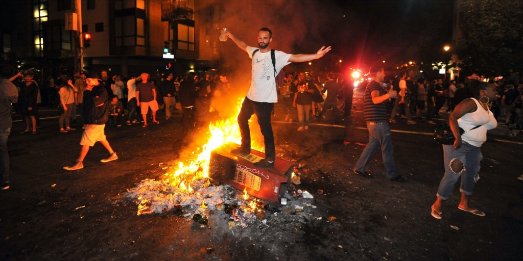 A man stands atop a burning newspaper stand in San Francisco's Mission district in California after the San Francisco Giants beat the Kansas City Royals in the World Series on October 29, 2014. A celebratory mood set the stage for what eventually became a scene of bottle throwing, vandalism, and bonfires throughout the area. AFP PHOTO/JOSH EDELSON (Photo credit should read Josh Edelson/AFP/Getty Images)
