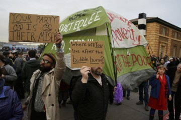 People hold up signs and a tent during a protest to demand city officials do more to help homeless people outside Super Bowl City, a pro-football's weeklong theme park near the famed Ferry Building in San Francisco on Wednesday, Feb. 3, 2016. Dozens protested what they say is San Francisco Mayor Ed Lee's plan to push homeless people out of the scenic bay-front Embarcadero, where Super Bowl festivities are being held. (AP Photo/Eric Risberg)