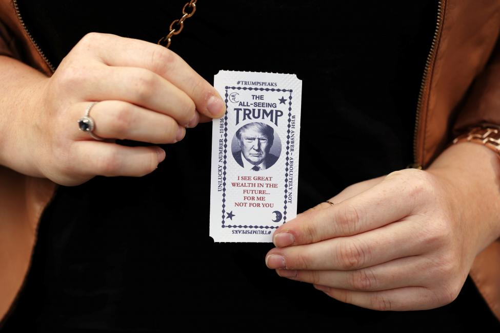 "A woman holds a ticket dispensed from a Donald Trump themed fortune telling machine. The machine tells people that they ""look poor"" and that they should let a ""rich puppet tell their future"". When a button is pushed it prints out a card with a ""misfortune"". REUTERS/Lucas Jackson"