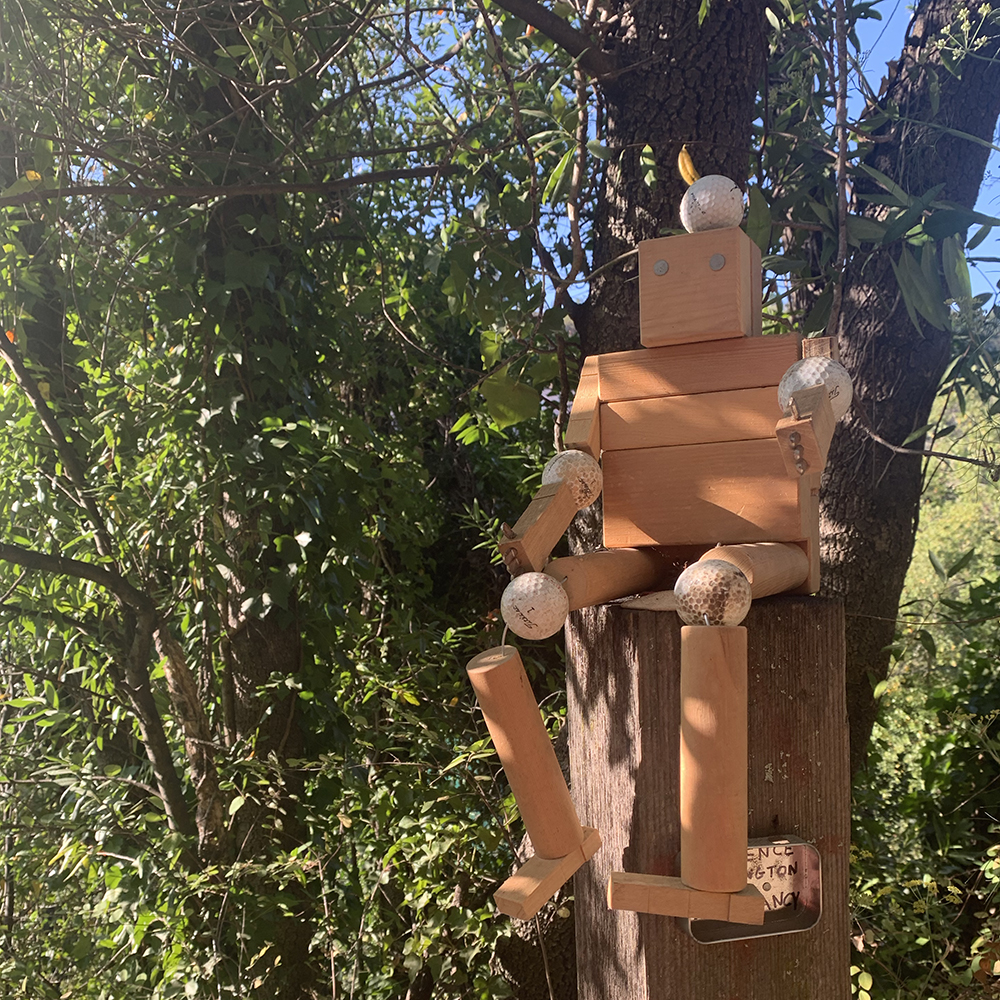 stoic troll made of all wood and golf balls sits on a perch